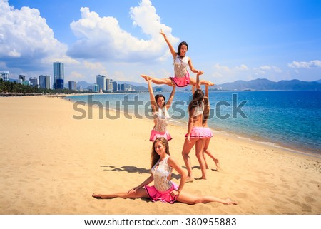 cheerleaders in white pink uniform perform High Straddle Stunt on sand beach against sea wind shakes long hair - stock photo