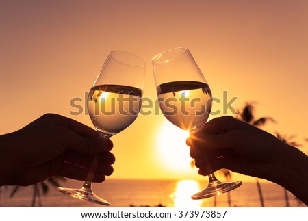Cheers against a sunset.  - stock photo