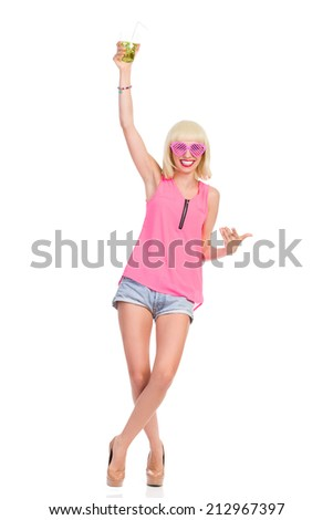 Cheers! Carefree blonde young woman in high heels, pink top and jeans shorts raising hand with lime drink. Full length studio shot isolated on white. - stock photo