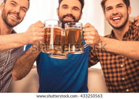 cheers! Close up photo of handsome men celebrating  and clinking glass of beer - stock photo