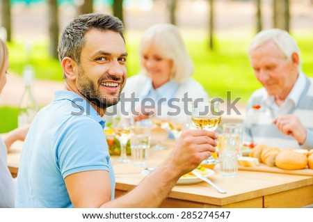 Cheers! Happy young man toasting with wine and smiling while sitting together with his family outdoors  - stock photo
