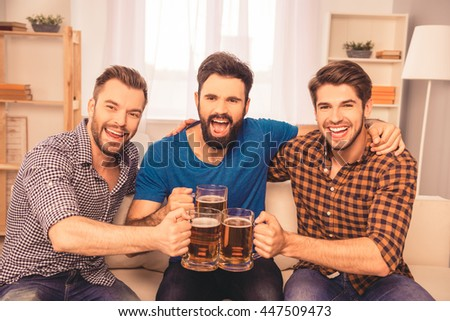 cheers! photo of handsome men celebrating victory and clinking glass of beer - stock photo