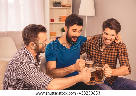 cheers! photo of happy  men celebrating and clinking glass of beer - stock photo