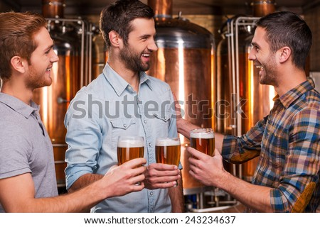 Cheers to friends! Three cheerful young men in casual wear talking to each other and smiling while holding glasses with beer and standing in brewery - stock photo