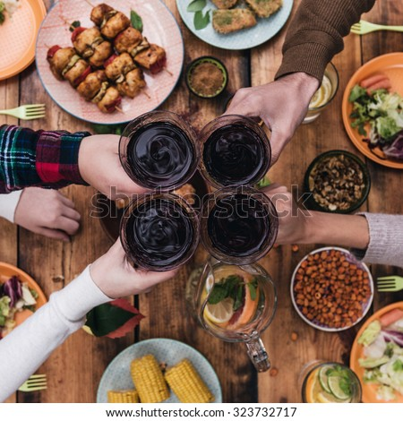 Cheers to friends! Top view of four people cheering with red wine while sitting at the rustic dining table - stock photo
