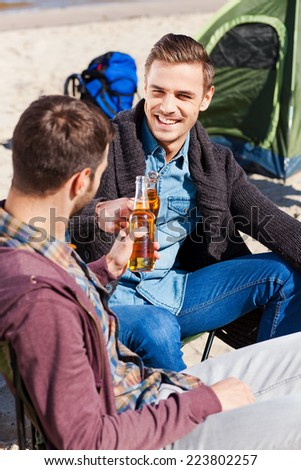Cheers to friendship! Top view of two handsome young men cheering with beer and smiling while sitting near the tent and on the sand - stock photo