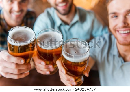 Cheers to success! Top view of three happy young men in casual wear toasting with beer while sitting in bar together - stock photo