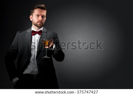 Cheers-Young man holding a tall cocktail glass on dark grey background - stock photo