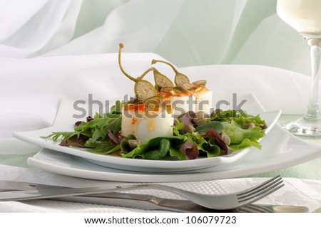Cheese and capers sweet and sour sauce and pistachios in the green leaves with a glass of white wine - stock photo