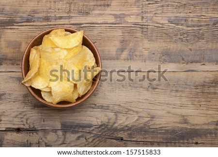 Cheese and chive potato crisp snack in brown bowl on wooden background - stock photo