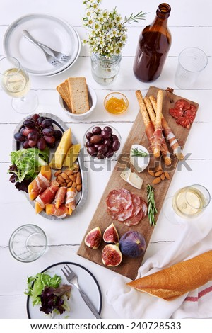 Cheese and cured meat charcuterie selection salami, chorizo, prosciutto wrapped bread sticks with fresh fig, rockmelon, almonds and white wine - stock photo