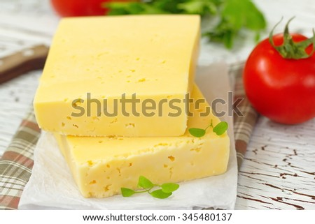 Cheese and fresh vegetables on the table - stock photo