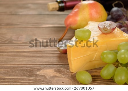 Cheese and grapes on a brown background - stock photo