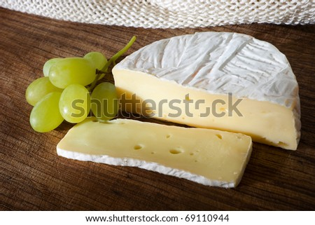 cheese and grapes on wooden board - stock photo