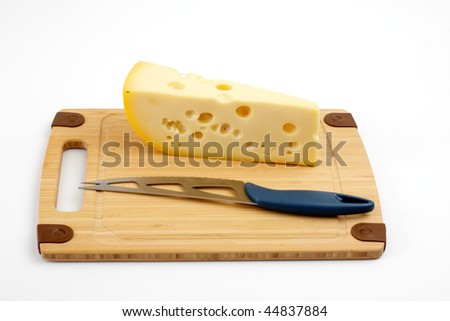 Cheese and knife on a wooden board, studio isolated - stock photo