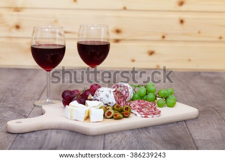Cheese and meat with glasses of red wine. - stock photo