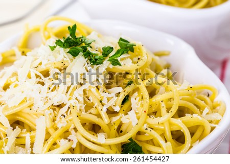 Cheese and pepper spaghetty with green garnish in white bowls. - stock photo