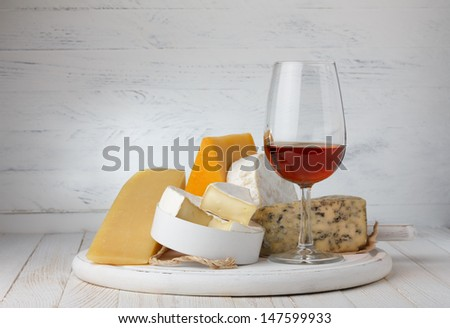 Cheese and red wine on wooden table still life - stock photo