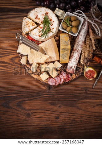 Cheese and salami arrangement served on cutting board. Shot from aerial view - stock photo