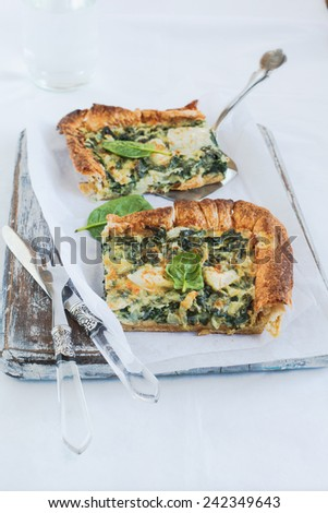 Cheese and spinach quiche pie pieces on a wooden board  - stock photo