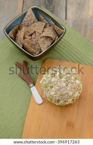 Cheese Ball with a Cheese Spreader for a festive party appetizer on rustic table - stock photo