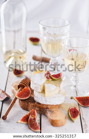 Cheese Board,appetizer.Brie ,Camembert cheese,figs,honey and thyme and white wine.selective focus - stock photo