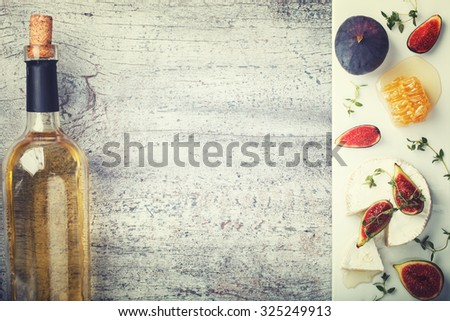 Cheese Board,appetizer.Brie cheese,bottle of white wine,figs,honey and thyme and white wine.Copy space.Toned image. Vintage style.selective focus - stock photo