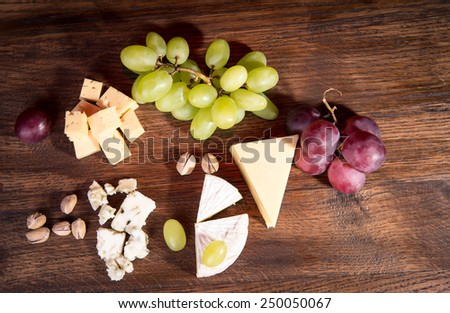 Cheese board. Various types of cheese. Cheese plate with cheeses Parmesan, Brie, Camembert and Roquefort in serving on the table from an old tree. - stock photo