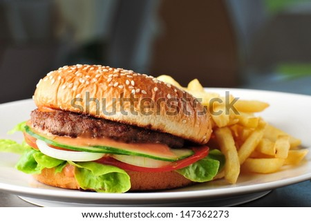 Cheese burger - American cheese burger with fresh salad and french fries - stock photo