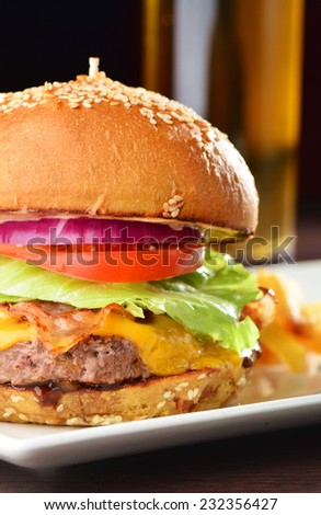 Cheese burger with a bacon - American cheese burger with fresh salad and french fries  - stock photo