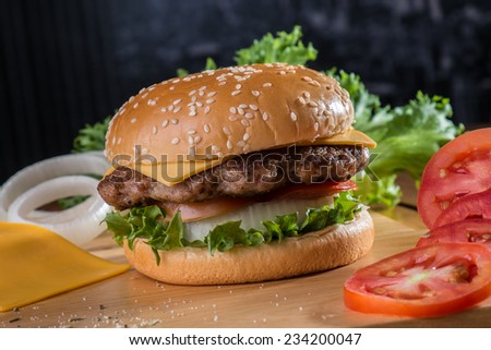 Cheese burger with ingredients around - stock photo