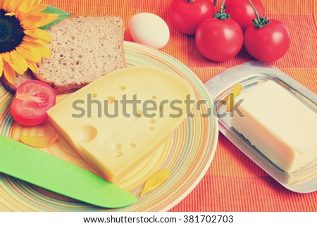Cheese, butter, boiled eggs, sliced rye bread with bran and fresh tomatoes. Mediterranean farm (country) food for breakfast served on a bright color napkin. Image done in retro instagram style - stock photo
