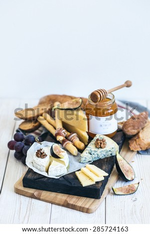 Cheese, figs, bread and honey on wooden background - stock photo