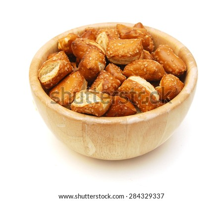 Cheese filled, bite-sized pretzel sticks in wooden bowl on white background  - stock photo