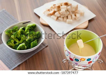 Cheese fondue with bread and broccoli - stock photo