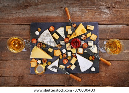 Cheese for tasting on wooden background, top view - stock photo
