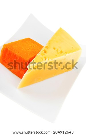 cheese : french gourmet triangles of yellow parmesan and orange cheddar on a plate isolated over white background - stock photo