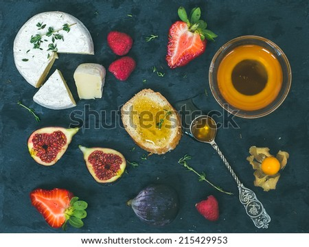 Cheese, fresh strawberries, figs, raspberries, ground cherry, thyme a slice of bread and a small bowl of honey with a tea-spoon on a dark stone board - stock photo