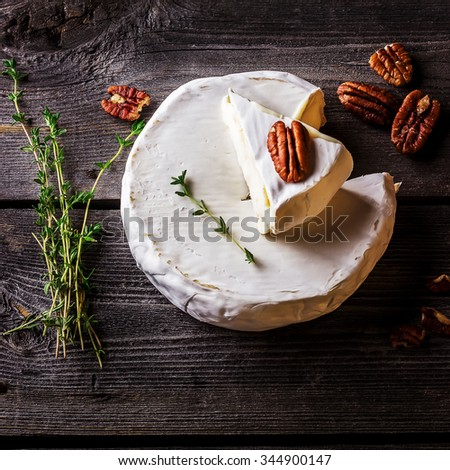 Cheese, herbs and nuts  on dark wooden table. Overhead view. Selective focus.  - stock photo
