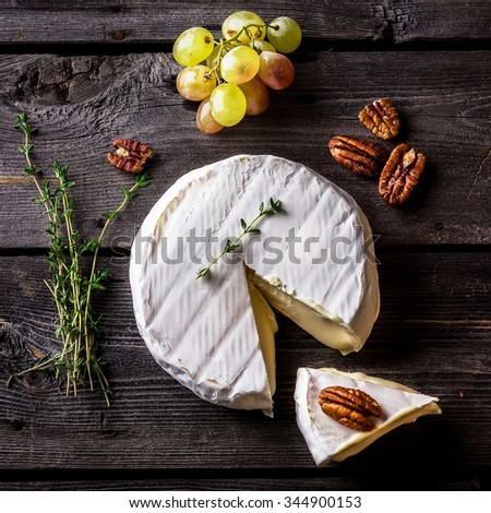Cheese, herbs, nuts and green grape on dark wooden table. Overhead view. Selective fucus. - stock photo