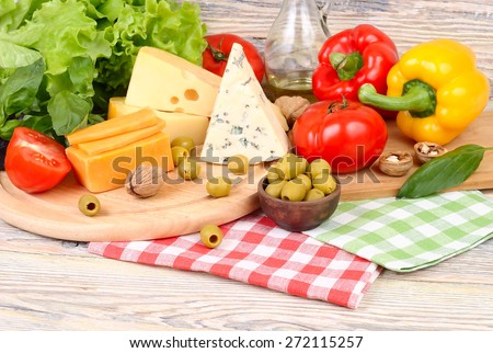 Cheese of various grades, fresh vegetables and olives on a light wooden background. Ingredients for preparation of the Italian vegetarian pizza. - stock photo