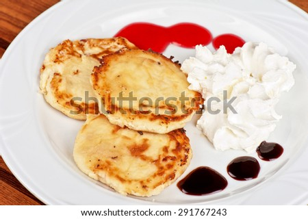 Cheese pancakes with sour cream and berry jam - stock photo
