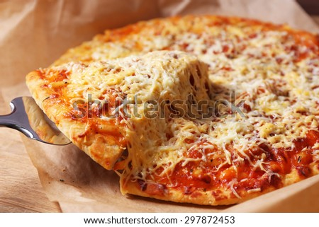 Cheese pizza on parchment with blade, closeup - stock photo