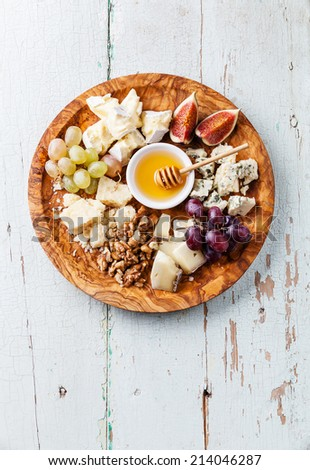 Cheese plate Assortment of various types of cheese on olive wood plate - stock photo