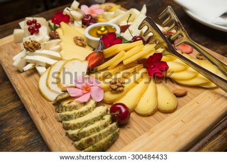 Cheese plate Assortment of various types of cheese on wooden cutting board, selective focus - stock photo