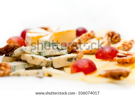 Cheese plate isolated on a white background decorated with red grapes. A series of food in a restaurant close-up - stock photo