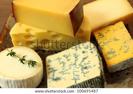 Cheese plate - various types of soft and hard cheese. - stock photo