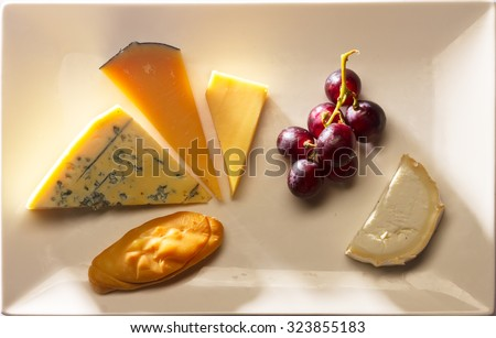 cheese plate with cheddar, oscypek, roquefort, old amsterdam and neufchatel cheese - stock photo