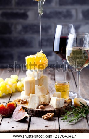 Cheese plate with honey, nuts and grape and white and red wine in glasses on a wooden background - stock photo