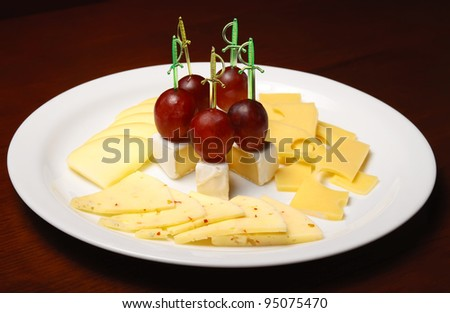 Cheese platter decorated with grapes - stock photo